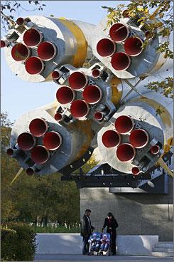 Vadim and Elena Smirnov walk their twins near the Soyuz rocket installed in central Baikonur, Kazakhstan, as a symbol of the Soviet Space program.