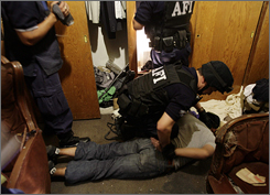 Members of Mexico's Federal Investigative Agency arrest a man on suspicion of drug possession Wednesday in Mexico City.