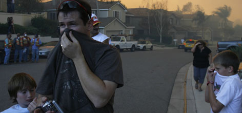 People cover their mouths to protect their lungs from the thick smoke from wildfires in Foothill Ranch, Calif.