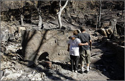 Patricia Foley and her nephew look at Foley's burned out home near Santa Clarita, Calif. Foley owned two homes on the property that were a total loss.