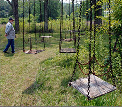Gaylord White strolls past a swing ride at the old Lake Shawnee Amusement Park near Princeton, W. Va. White owns the once popular summertime retreat which is now better known as a purported gathering place for the spirits of deceased locals.