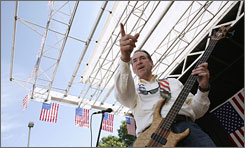 Mike Huckabee, former governor of Arkansas and current White House hopeful, gestures to supporters while playing bass in his band, Capitol Offense, during the Iowa Straw Poll in Ames, Iowa, on August 11.