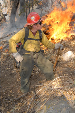 Firefighter Anna Kelly, 24, works the mountainside near Running Springs, Calif., the site of the Slide Fire.
