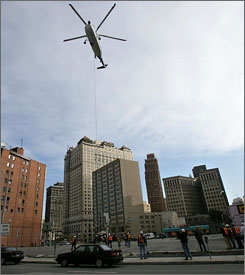 A helicopter in Detroit lifts equipment from the ground to the top of the building that used to be Book-Cadillac Hotel. The structure is being restored to open next year as the West Book Cadillac Detroit.