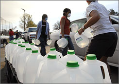 Ramona, Calif., residents line up to receive bottled water Friday because other water use was not allowed. Many residents and volunteers elected to wear face masks because the air remained smoky.