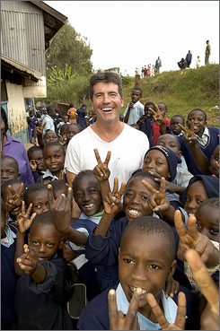 Simon Cowell smiles with children in Africa. The funds raised by a special American Idol show April 24 are making their way to the children in need.