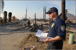 Sgt. Eric Charlick from the California Department of Insurance distributes flierswith guidance on rebuilding.