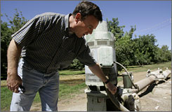 Gary Barton shows a pump on his farm in Ripon, Calif., in August. Thieves hit Barton's walnut farm twice last spring, stripping copper from irrigation pumps and power poles.