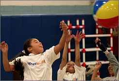 Cierra Agosto, left, and Katherine Rojas, center, play with a beach ball during P.E. class at P.S. 57 in New York City on Thursday.