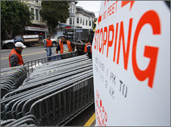 City of San Francisco Public Works employees unload and stack police barricades along Castro Street.