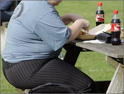 An overweight person eats in London. Britain's health secretary has called for a fundamental shift in the way the nation tackles obesity after a study said dramatic action was required to stop the majority of the population from becoming obese by 2050.