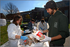 University of Vermont student eco-reps Meg Rice and Bill Ottman sort through one day's trash from the Davis Student Center on the Burlington campus to demonstrate what could have been recycled.