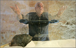 Egypt's antiquities chief, Zahi Hawass, presents mummy of King Tut in his underground tomb in the famed Valley of the Kings in Luxor, Egypt. The body was placed in a climate-controlled glass box in the tomb, with only the face and feet showing under the linen covering.