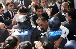 Pakistani riot police scuffle with lawyers during a protest in Lahore on Monday.