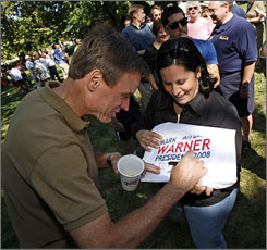 Former Democratic governor of Virginia Mark Warner signs a T-shirt for Julia Torres Barden in September. He is pursuing the seat being vacated by retiring Republican Sen. John Warner (no relation).