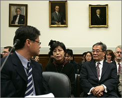 Yahoo CEO Jerry Yang looks at Gao Qin Sheng, mother of Shi Tao, a Chinese reporter who imprisoned for leaking state secrets, and Chinese dissident Harry Wu, right, as he testifies before a House Foreign Affairs Committee hearing on Tuesday. Yang offered his apology to the families affected by Yahoo's cooperation with the Chinese government.