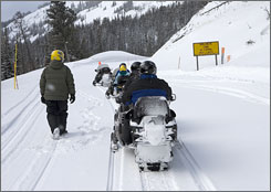 Snowmobiles pass a sign warning about the risk of avalanches on Sylvan Pass on Dec. 25. The park spent $120,000 to $200,000 to maintain the pass last winter.