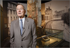 Former President George W. Bush looks over an exhibit at his presidential library showing a section of the Berlin Wall and the historical period of the Berlin Wall being torn down.