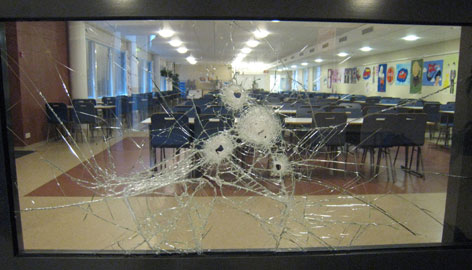 Photo released by Finland's National Bureau of Investigation shows bullet holes in a glass panel on the first floor of the Jokela high school in Finland.