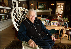 Norman Mailer sits in front of family photos at his home in Provincetown, Mass. He believed in the supremacy of fiction over fact, but he wrote some of his best work as the &quot;New Journalism&quot; movement emerged in the mid-1960s. He pioneered subjective reporting that read like a novel. 