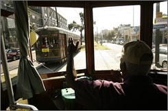 Streetcar operator Lawrence Galloway, a 30-year veteran, waves to a fellow operator as the St. Charles line readies to open this past weekend. The 1920s-era cars run along tracks laid down in the 1830s.