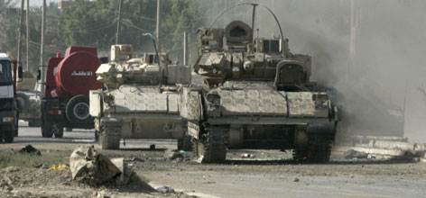 A U.S. armored vehicle that was damaged in a roadside bomb attack remains on a road in Baladyat district in Baghdad, on Sunday.