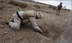 U.S. Marine engineers search for roadside bombs near a U.S. military base outside the western Iraq town of Hit last year. The Marines were patrolling the area in search of hidden weapons caches, improvised explosive devices and insurgent activity.