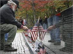 A veteran plants a flag Saturday at the Vietnam Veterans Memorial in Washington, D.C.