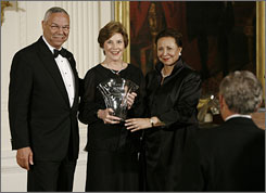 Former U.S. Secretary of State Colin Powell and his wife Alma present an award to first lady Laura Bush at a ceremony at the White House in Washington, D.C., Tuesday. President Bush applauds with his back to camera.