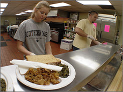 University of Southern Mississippi students Karen Allred of Meridian, Miss., and Brett Dyar of Purvis, Miss., help serve lunch at the Christian Services Soup Kitchen in Hattiesburg, Miss. Mississippi had the highest rate of families who went hungry in 2006.
