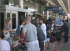 Air travelers line up for curbside check-in as they arrive at O'Hare International Airport on July 2. On-time performance for airlines is the lowest it's been since at least 1995.