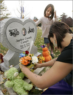 Carly Moore and her daughter, Taylor Glatzer, 6, place flowers at the grave site of Carly's son, Jayden Cangro, in Salt Lake City. The child died from injuries suffered in July 2006 after Moore's then-boyfriend, Phillip Guymon, hurled the 2-year-old nine feet across a room.