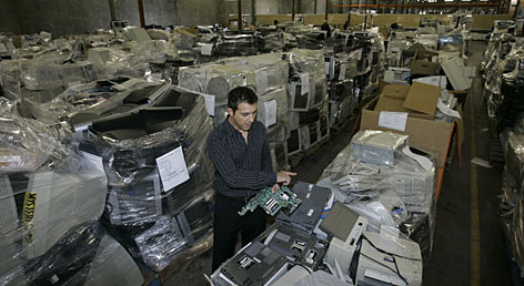 John Bekiaris, chief executive of HMR USA, sorts through discarded computers at a warehouse in Brisbane, Calif.