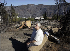 Nancy Goauthier points to her destroyed house as she rests after picking up what was left from her home on Lockwood Road, in Malibu, Calif., after a wildfire swept through the neighborhood Saturday.