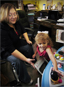 """""""I learn more this way"""": Single mother Hannah Cross, 22, plays with her daughter, Haleigh. Cross is a student  at the University of Arkansas at Fort Smith who has taken many of her courses online."""