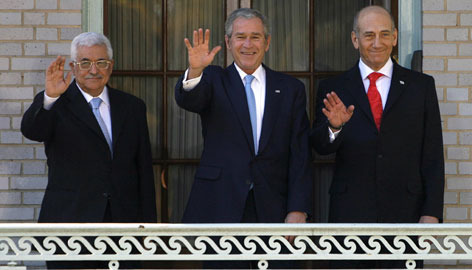 President Bush, center, waves as he hosts a meeting with Israeli Prime Minister Ehud Olmert, right, and Palestinian President Mahmoud Abbas, left.