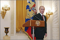"Russia's President Vladimir Putin stands at a podium as he meets foreign ambassadors in Moscow's Kremlin, Wednesday. Putin, who steps down next year, urged Russians that taking for granted the country's economic development is a ""dangerous illusion."""