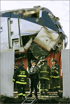 Chicago firefighters work at the scene where an Amtrak train plowed on top of a freight train in Chicago.