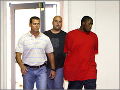 Investigators walk Venjah Hunte, right, 19, a suspect in the murder of Washington Redskins star Sean Taylor into the Florida Highway Patrol offices in Fort Myers, Fla. on Friday.