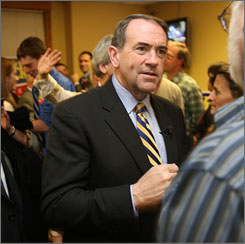 Former Arkansas governor Mike Huckabee, speaking to a supporter in New Hampshire, has drawn support from conservatives by opposing abortion rights and same-sex marriage.