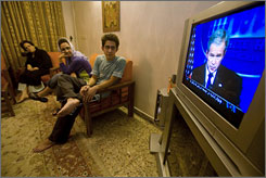 A family watches President Bush's news conference on the U.S. intelligence report, in Tehran.