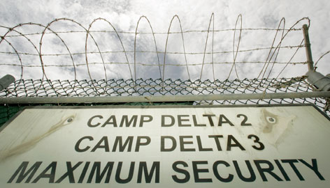 In this 2005 file photo reviewed by the U.S. military, a razor-wired fence is shown above the Camp Delta 2 and 3 base sign at Guantanamo Bay Naval Base in Cuba.