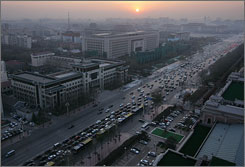 The sun sets over Beijing on Friday as rush hour traffic flows along Chang'An Avenue, the city's main east-west artery. China's auto market is now second only to the U.S., but the growing numbers of motorists have contributed to appalling air pollution in cities and a spike in energy consumption.