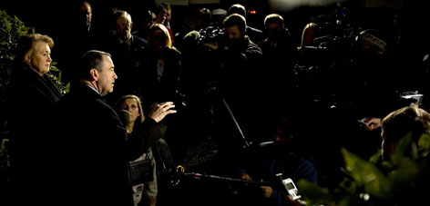 With wife Janet at his side, Republican presidential hopeful Mike Huckabee talks to the media on his way to a private fundraiser in Greensboro, N.C., on Thursday.
