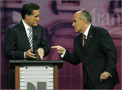 Mitt Romney, left, talks with fellow Republican presidential hopeful Rudy Giuliani, following a debate in Coral Gables, Fla.