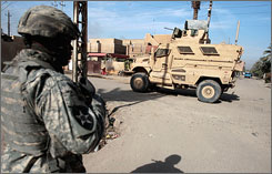 A soldier heads back to a Mine Resistant Ambush Protected vehicle, or MRAP, after a patrol in Baghdad.
