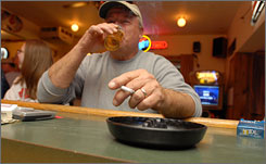 Lanny Krause, 58 of Winona, Minn., enjoys a cigarette at George's Lounge across the river in Wisconsin.