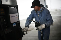 Trucker Randy Walker fills his rig's tanks with biodiesel fuel at a gas station in Nevada, Iowa, Dec. 6. The Senate approved a bill requiring increased auto efficiency and ethanol use, but the measure to tax oil companies was one vote short of overcoming a Republican filibuster.
