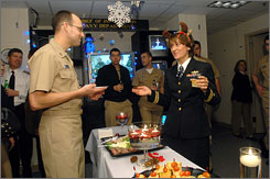 Navy Lt. Jay Boyles, left, and Navy Lt. Lara Bollinger, right, chat during the Navy Department of Information's office Christmas party on Thursday in Washington.