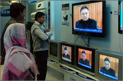 Pakistani people listen to the speech of President Pervez Musharraf being broadcast on radio and TV in Karachi on Saturday.